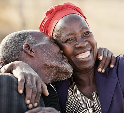 Man kissing woman with fixed dentures on her cheek
