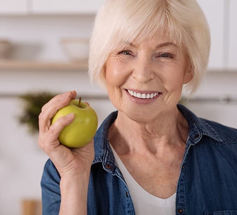 Smiling woman holding a green apple