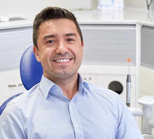 Man in dental chair smiling after oral cancer screening