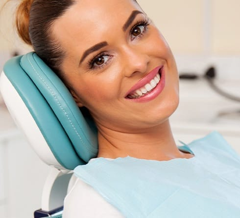 Woman smiling in dental chair after teeth whitening