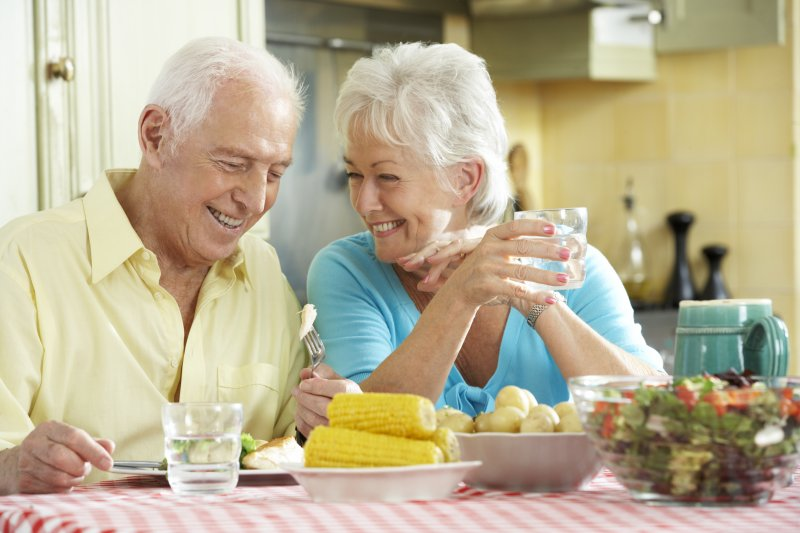 Couple smiling at table filled with summer foods