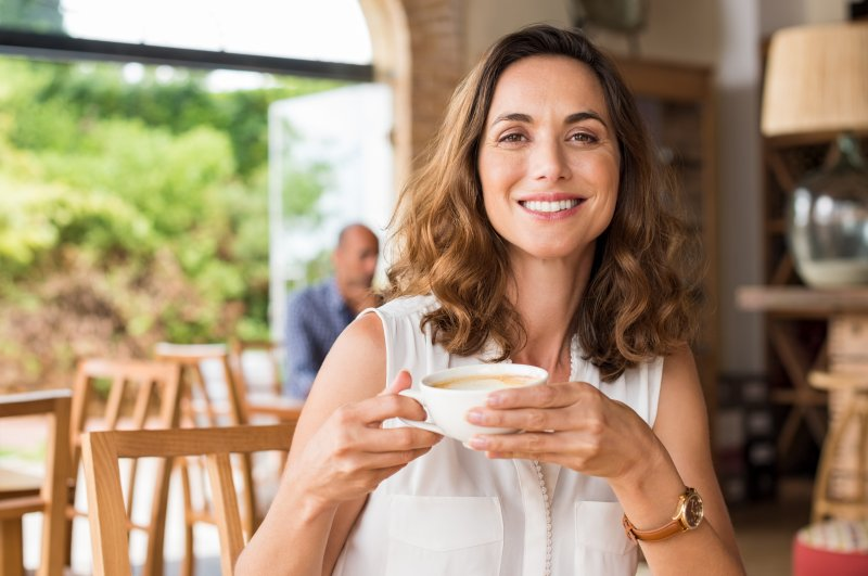 Woman with dental implants smiling while drinking coffee